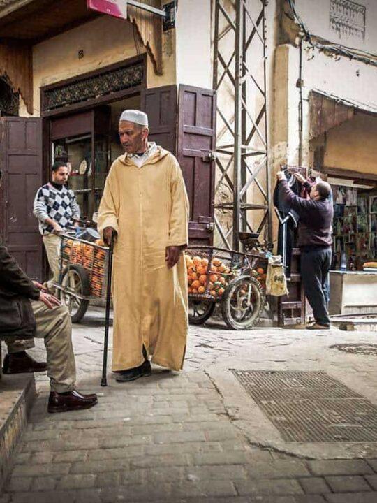 Man in traditional dress walking through Fez Medina