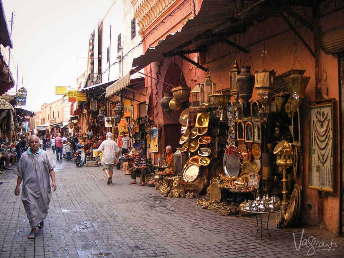 men walking past pot sellers in Marrakech Souk Morocco. Best free things to see and do in Marrakech Morocco