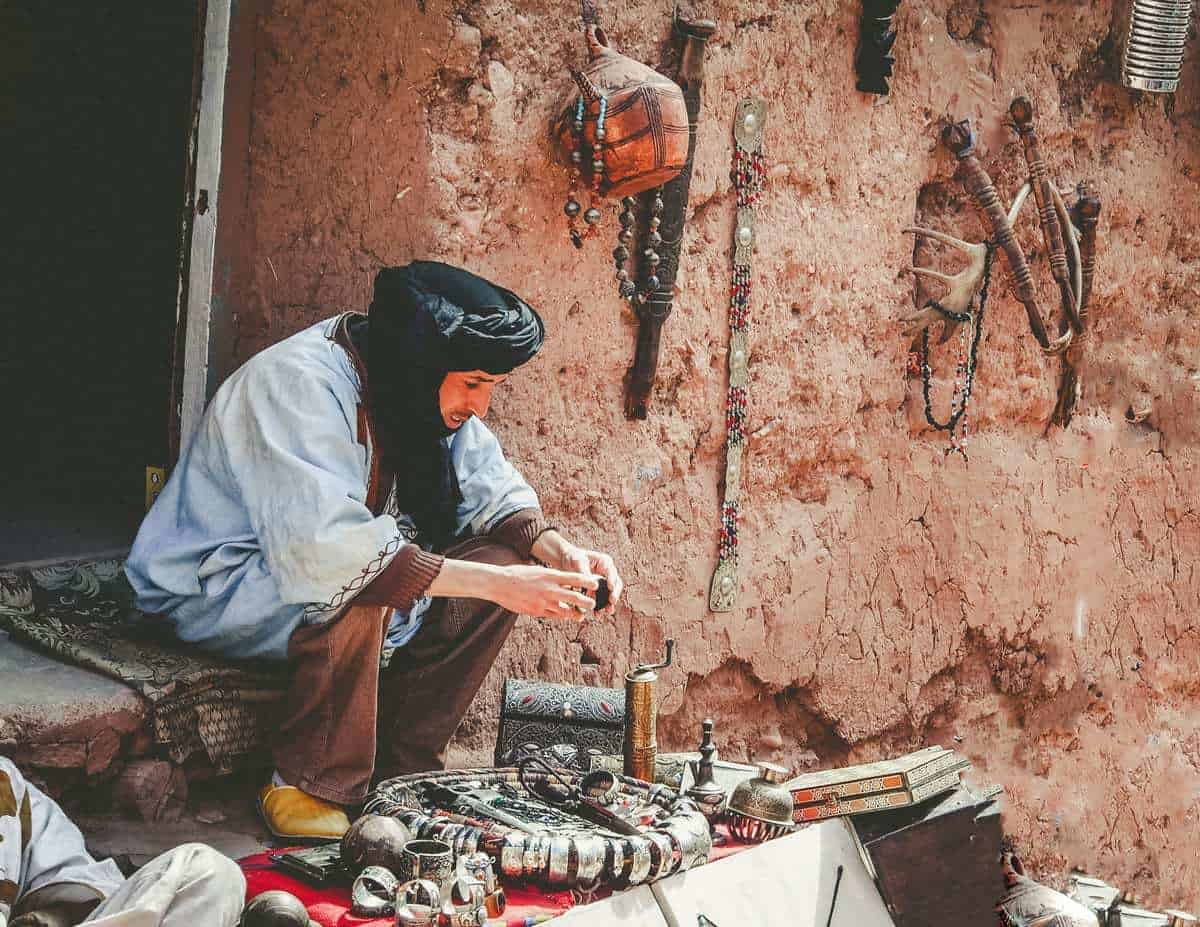 Seated Moroccan man making metal handicrafts in Ait Benhaddou Morocco. A great thing to see on a Moroccan Road Trip and to buy if you know how to haggle moroccan style.