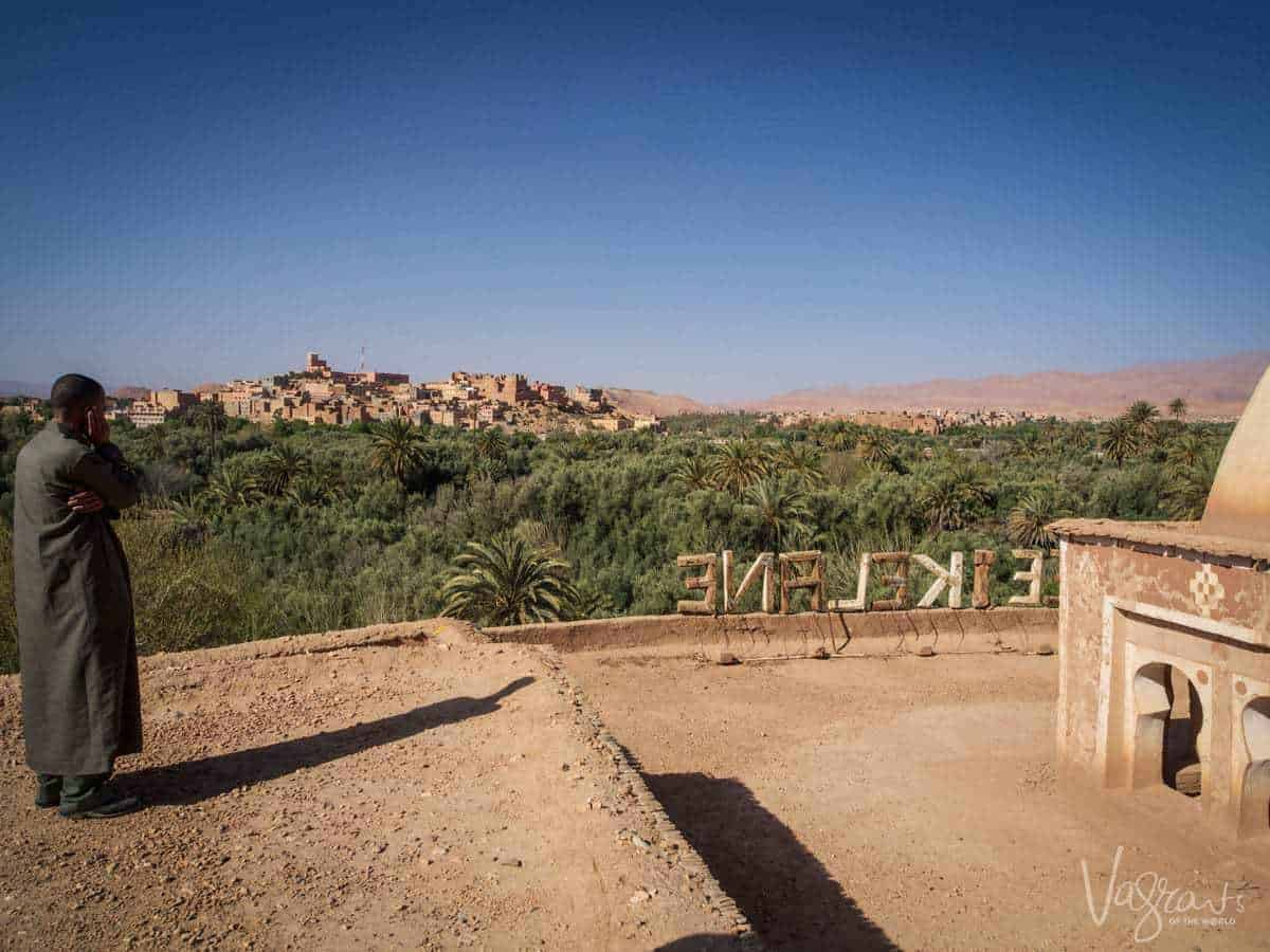 Moroccan Road trip guide - Marrakech to Fez -Man on rooftop looking out over Ouarzazate Morocco
