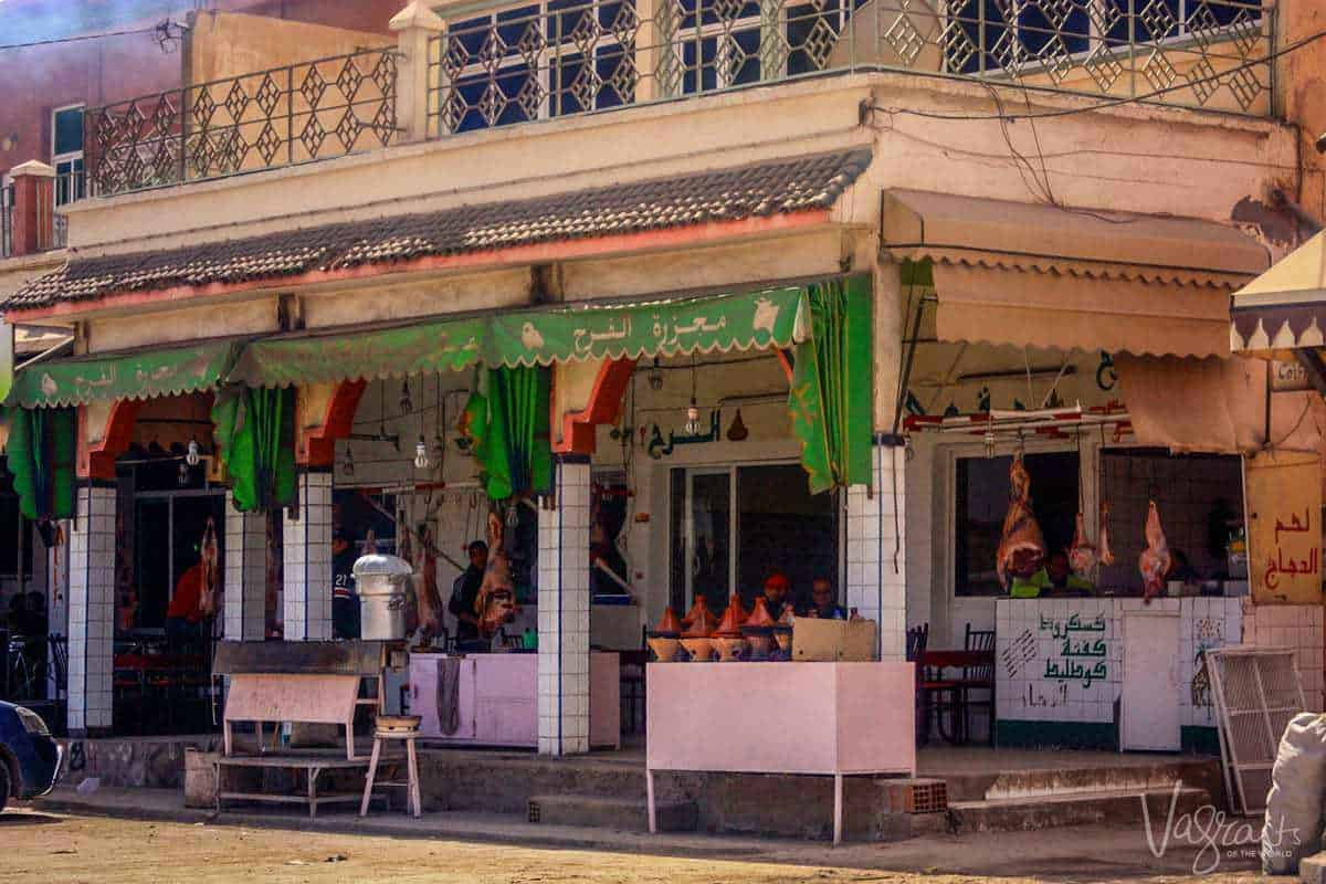 Restaurants in Zaida in the Midelt province Morocco with goat carcass hanging in the shop front and tagines ready to be cooked. The sights you see on a moroccan road trip.