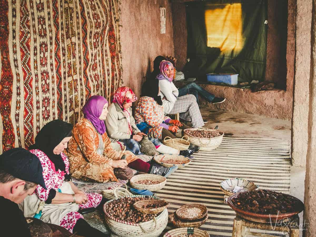 Woman sitting against a wall with large wicker baskets of coffee beans at a Womens co op Atlas Mountains Morocco