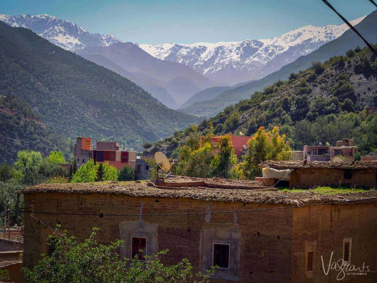 Marrakech to Fez Middle Atlas Mountains showing a roof top with snow covered mountains in the background. You get great views like this on a moroccan road trip