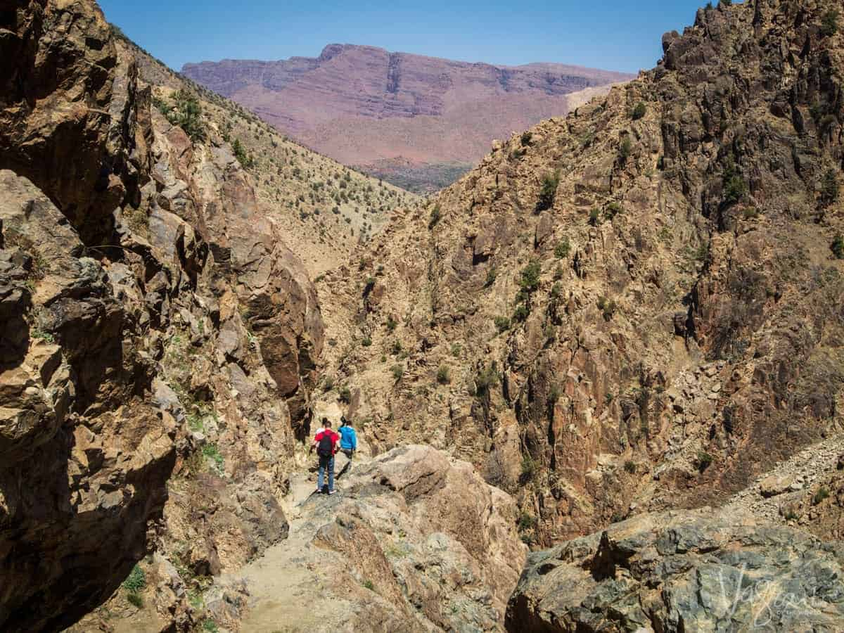 The Middle Atlas Mountains - people walking along a rocky path in the gorge.