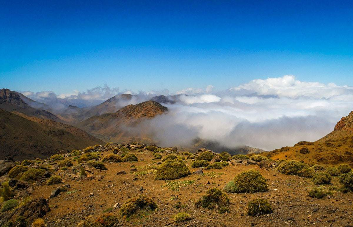 morocco road trip Marrakech to Fez Crossing the high Atlas Mountains with low cloud hovering over the mountain tops.