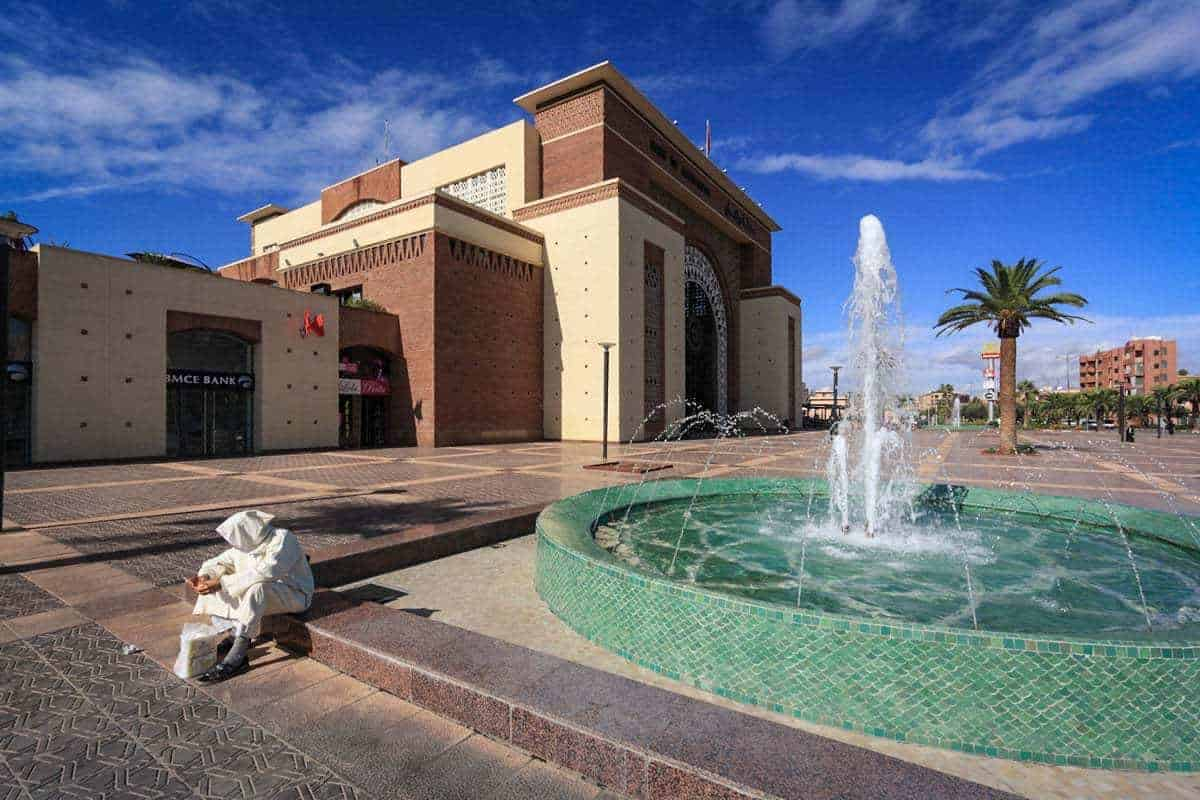 man in white garb sitting on fountain in new Town Marrakech Morocco. things to avoid in Marrakesh. Beware of scammers.