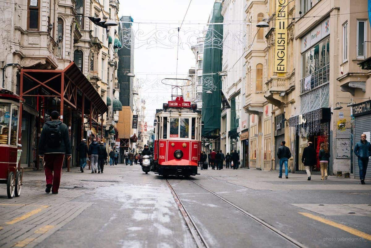 red tram heading down the centre of pedestrian street in taksim old city istanbul. this area is one of the best places to visit in istanbul