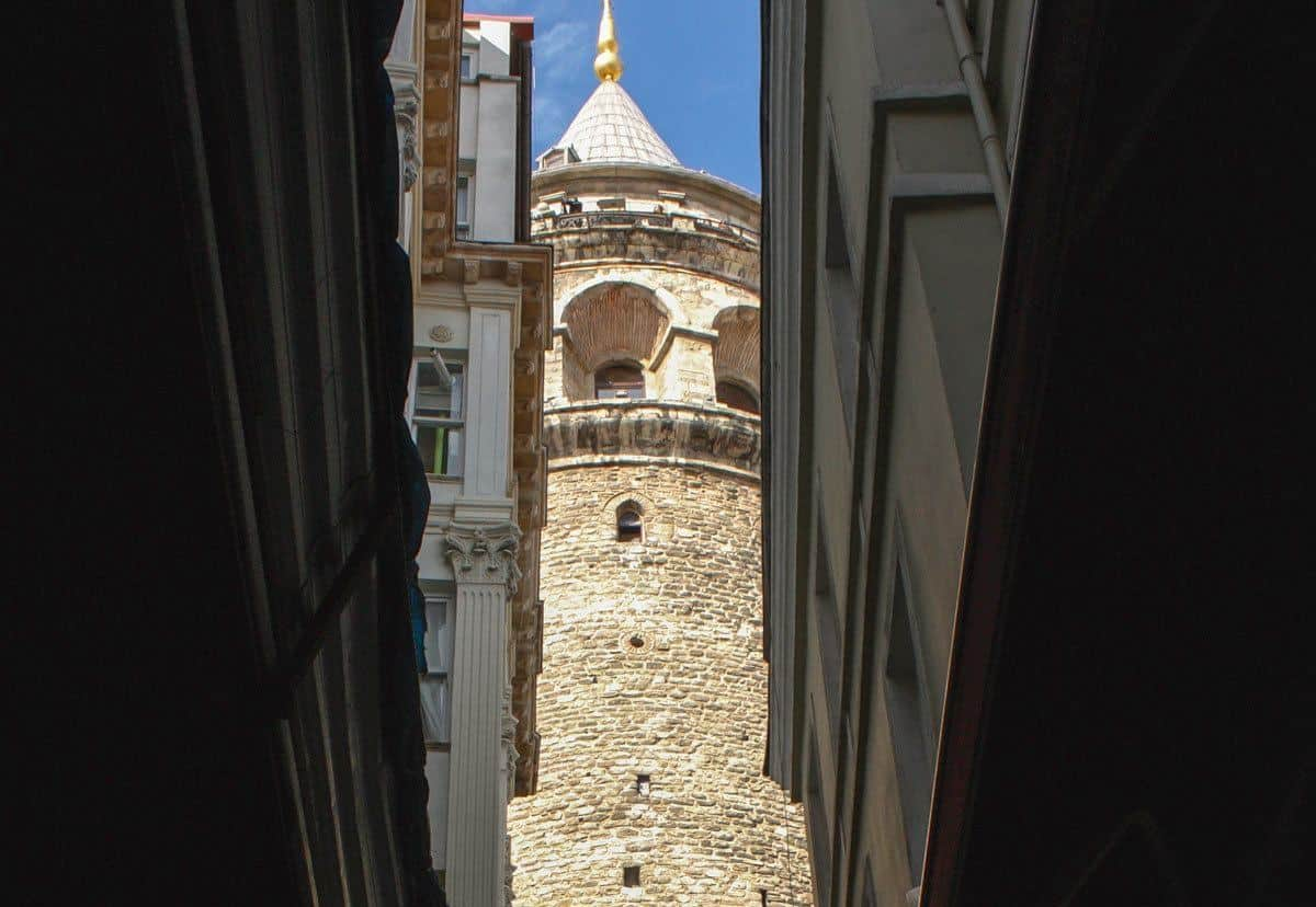 slim view of galata tower between two buildings. if you are looking for the best restaurants in istanbul then you will find them in this area.