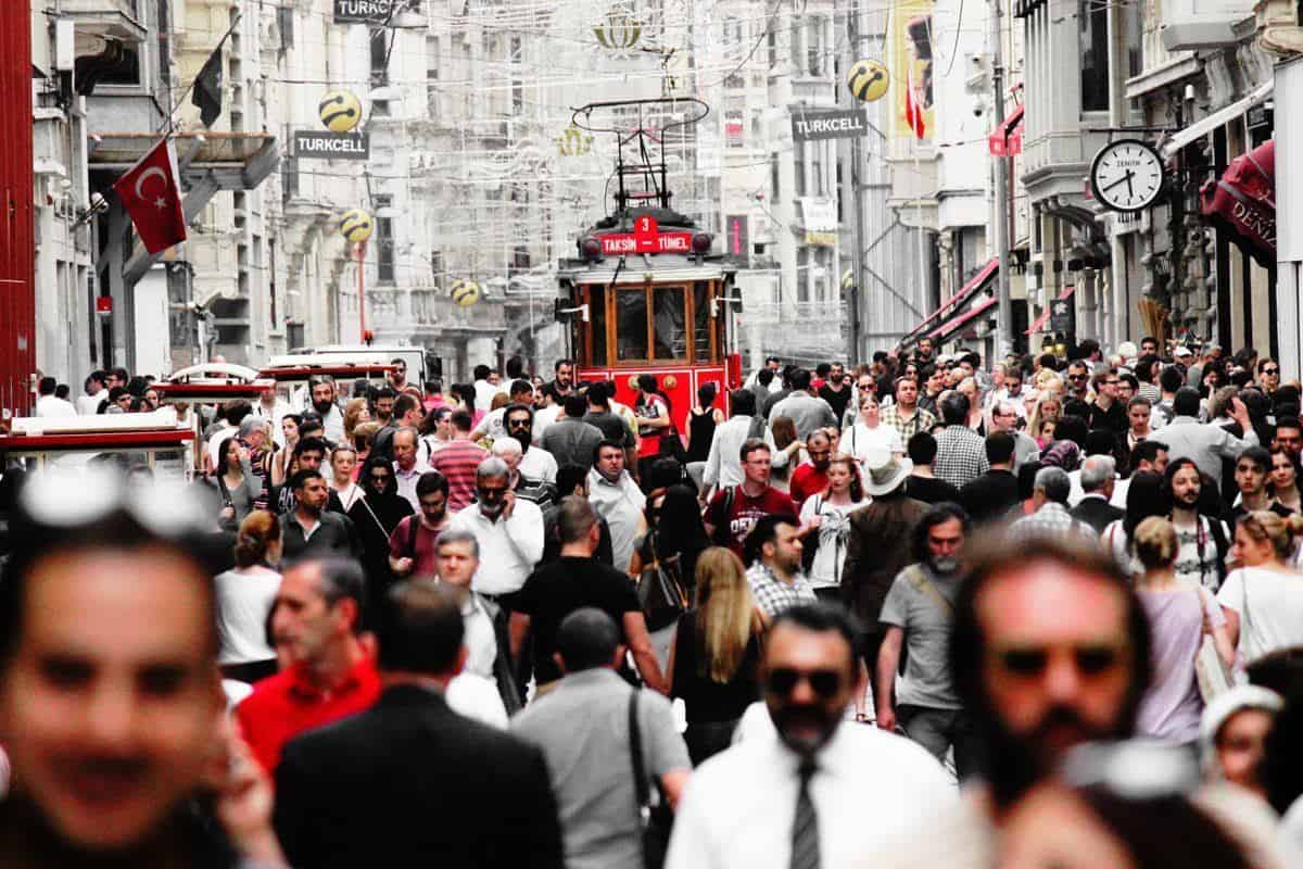 crowded street with tram coming through a throng of people, this is what it is like to live like a local in istanbul
