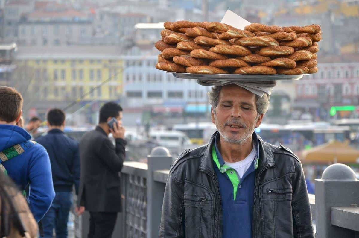 man carrying tray of bagels on his head. this may not be listed as an Istanbul attraction but these sights is what Istanbul sightseeing is all about