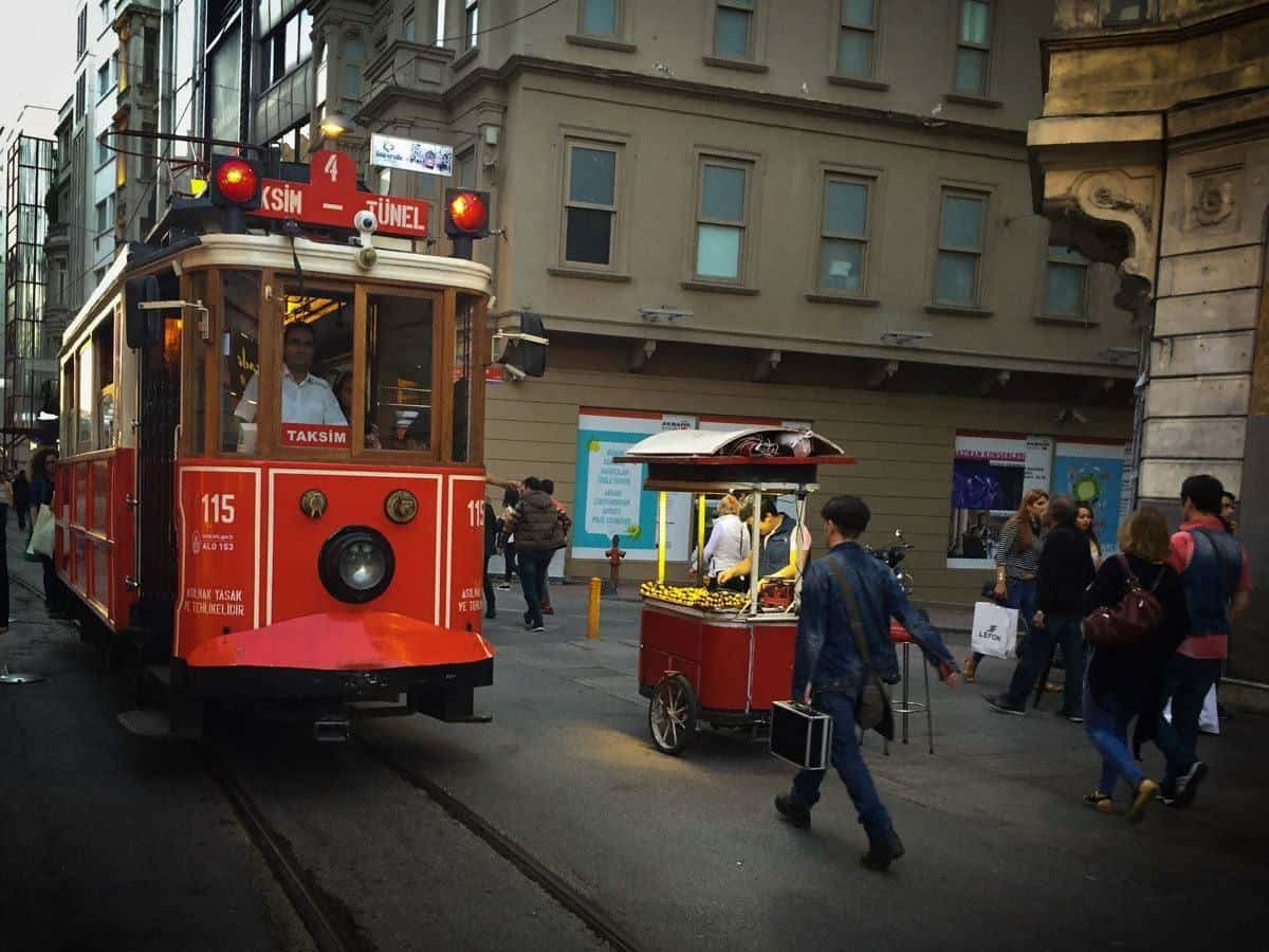 red tram coming past street stall seller. wandering the city is what you want to do in istanbul if you want to feel like a local.