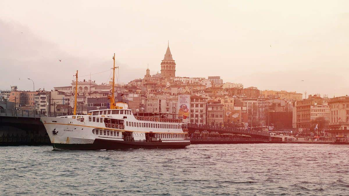 boat on a Bosphorus river cruise in istanbul with the city in the background. getting a good istanbul tour guide will ensure you don't miss the best of istanbul attractions