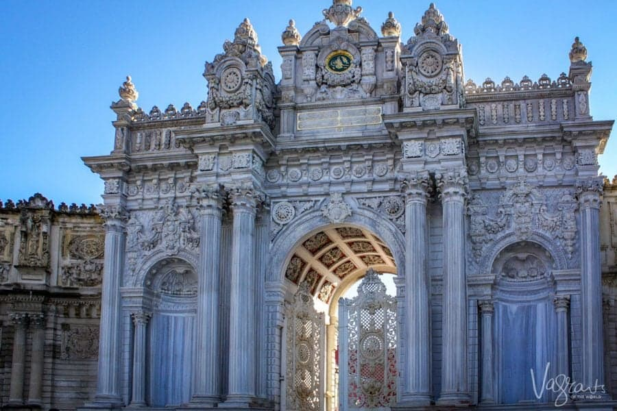 white and blue facade with columns and arched entry of Dolmabahçe Palace Istanbul Turkey. part of the attraction of visiting the old city and a great destination for sightseeing