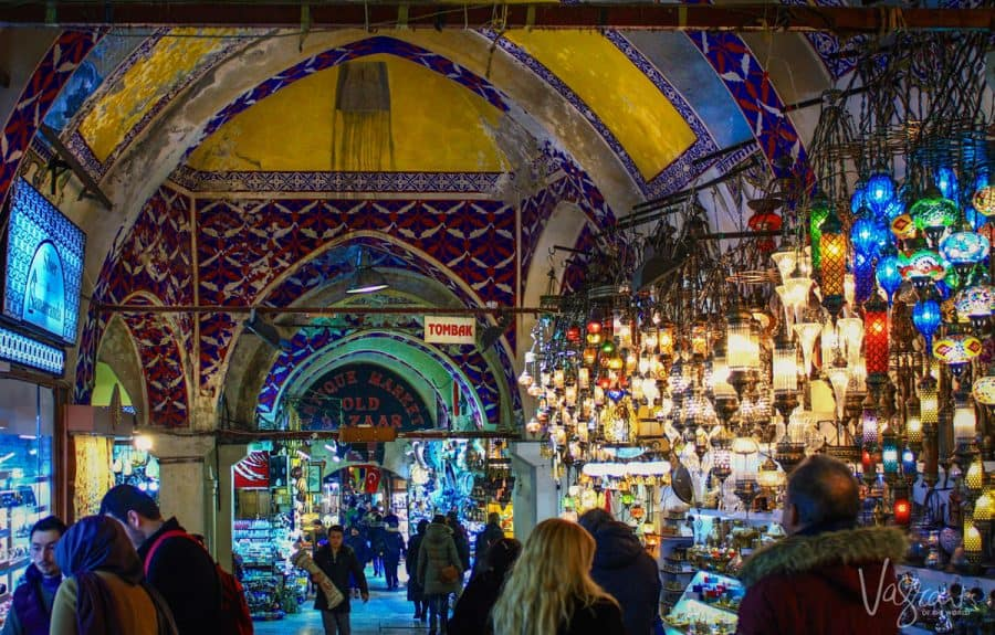 people walking into the Grand Bazaar Istanbul hundreds of lanterns in a display next to the entry. this is also a place where you will have no trouble deciding what to eat in istanbul