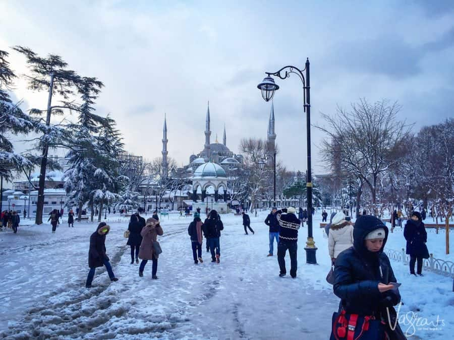 people carefully walking across the snow covered Sultanahmet Square, Istanbul Turkey. If you are wondering where to go in istanbul then this square is the best place to start and should be at the top of your istanbul itinerary.
