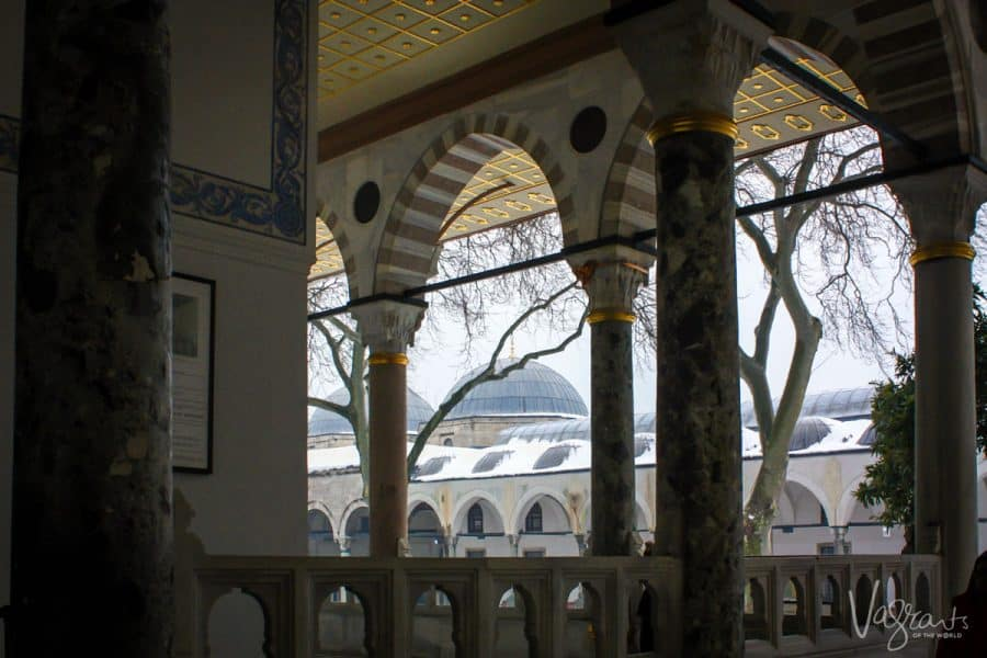 looking through the arches of Topkapi Palace at the blue mosque. tourists want to know where to go in istanbul and a visit to the palace is one of the best things to do in istanbul