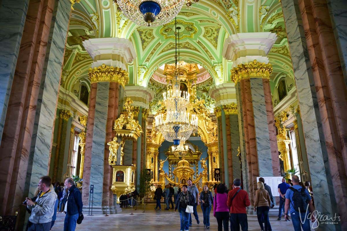 People inside the gold and green Peter and Paul Cathedral a must thing to see and do in st petersburg and should be on your russian itinerary.