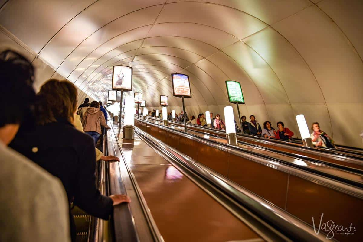 People riding the steep escalators, St Petersburg metro. Interesting things to see in St Petersburg are the metro stations