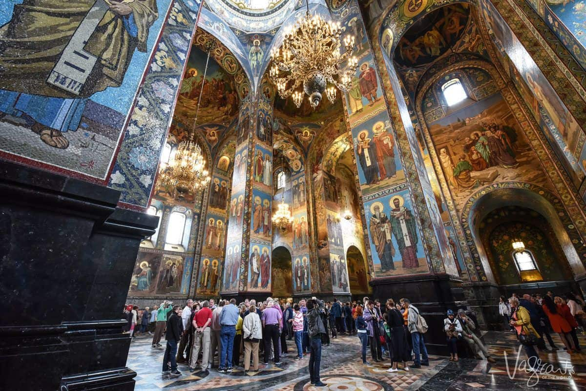 People admiring the paintings on the walled interior of the Church of our Saviour on Spilled Blood in St Petersburg Russia. One of the most awesome things to do in St Petersburg is to visit this church and learn of its macabre history.