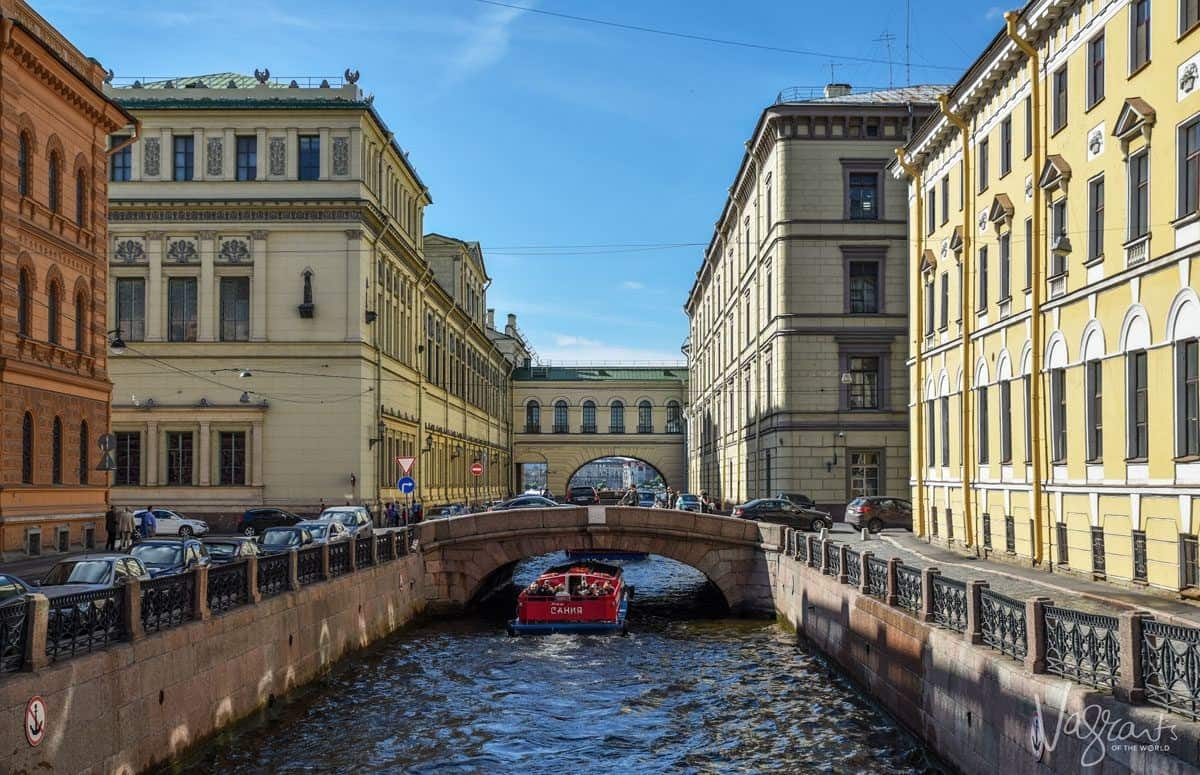 A Canal boat going under a bridge in the canals of St Petersburg.