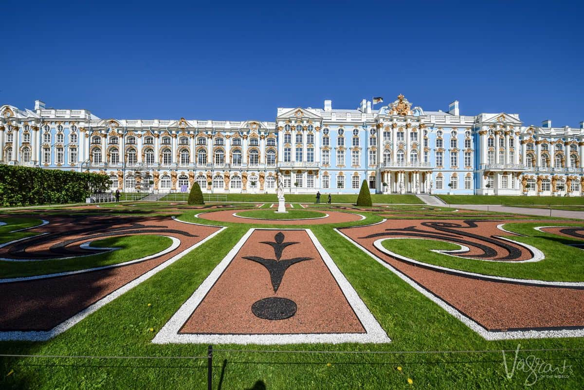 The blue and gold exterior of Catherine Palace and the ornate stone designs in the green grass foreground. a travel tip on how to see the best of st petersburg is to book some half day and one day tours so you see the best of st petersburg.