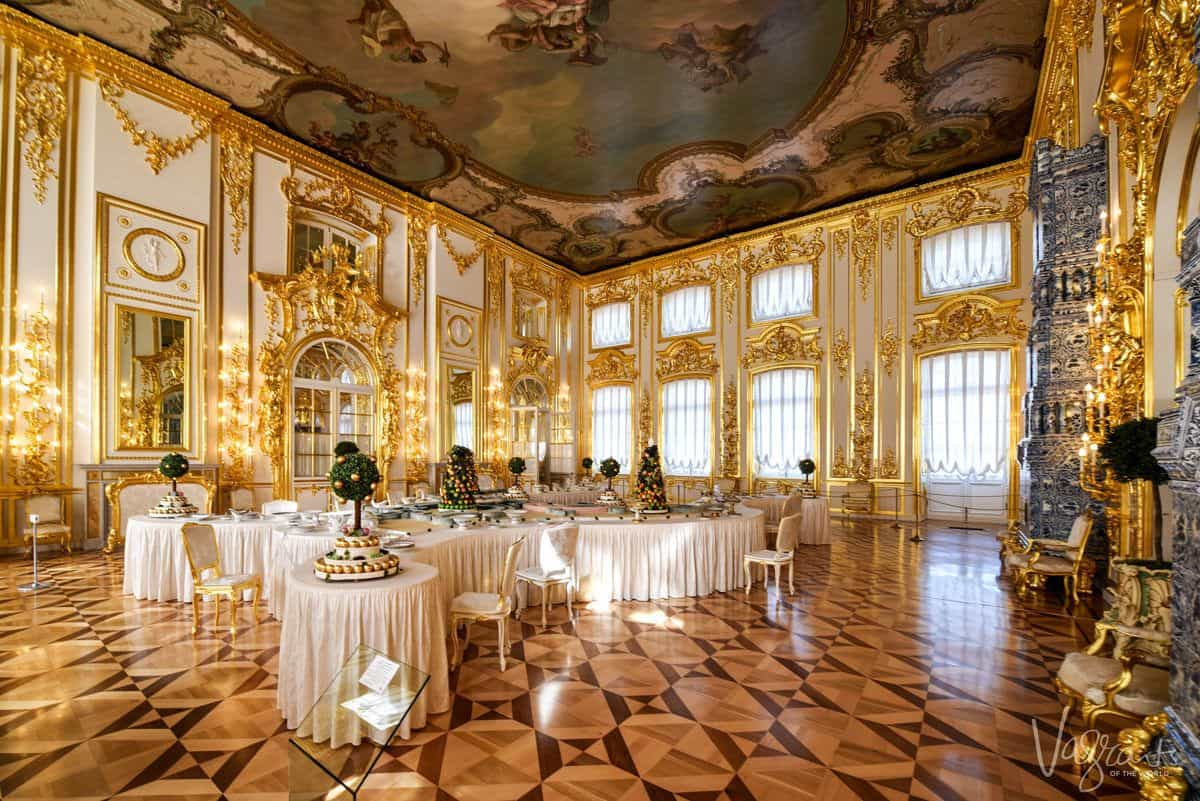 Gilded walls and windows surround the table settings for a grand meal. The palace is one of the best buildings to see in St Petersburg