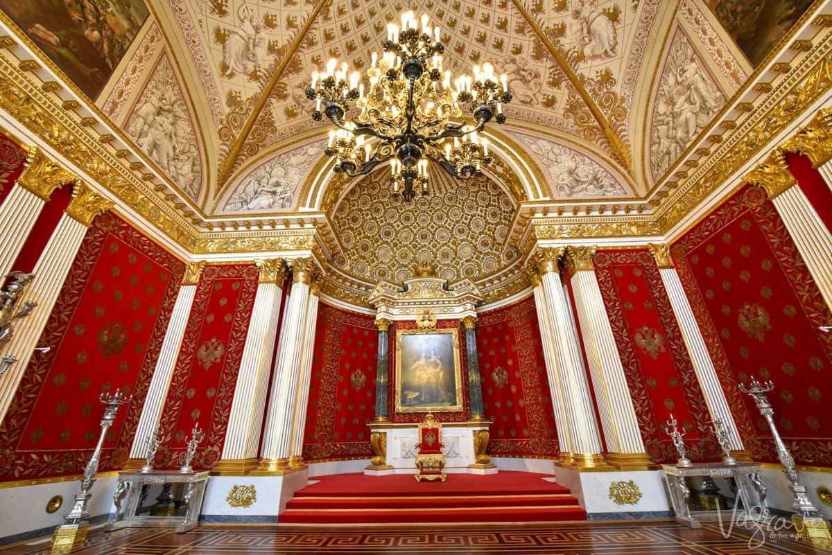 red walls, gold ceiling and chandelier before a portrait. one of the very best things to do in st petersburg is to visit the hermitage museum, but you need plenty of time so that you will find and enjoy some of the hidden gems in the hermitage museum
