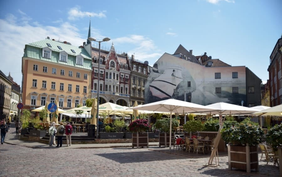 Cafes with colourful old buildings in the background in Old City Riga Latvia. There are plenty of great places to eat and drink in Riga making it a perfect city break.