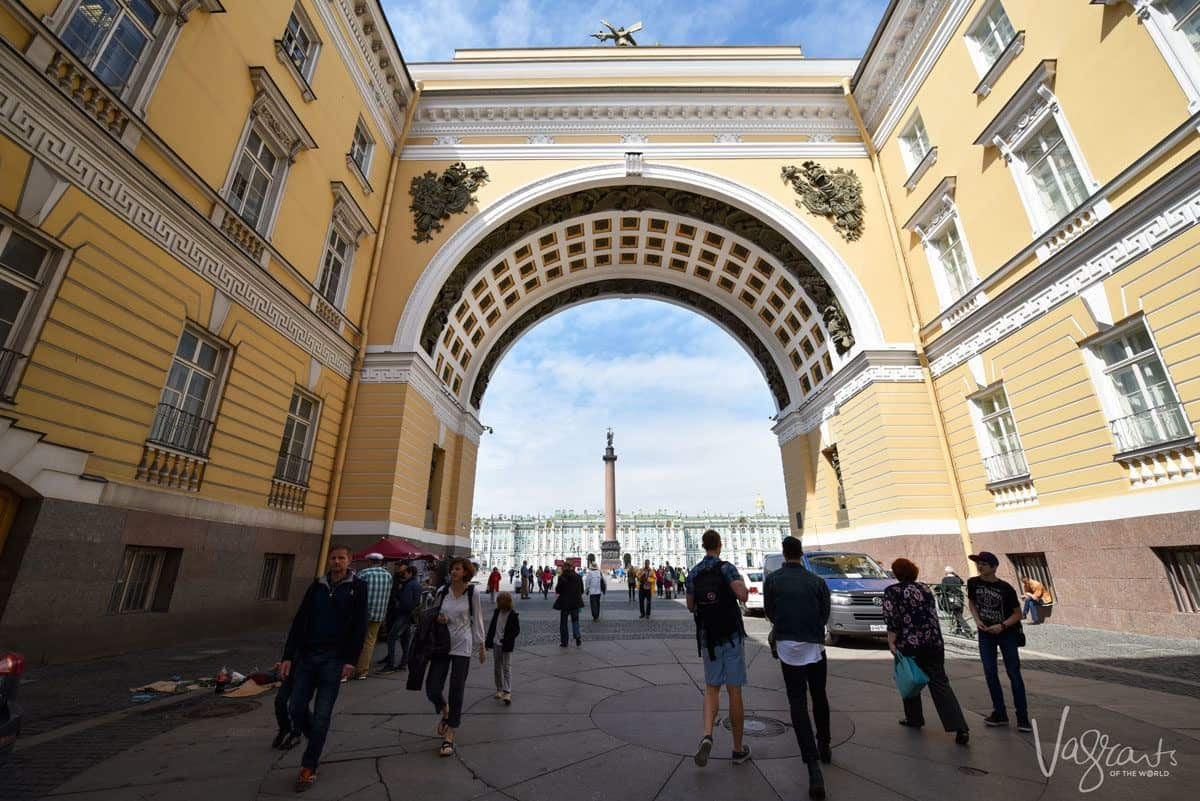 people walking under yellow archway in Moscow.  Getting around Russia is easy on a river cruise in Russia but you will need a russian visa.  We can also show you how to get a tourist visa for russia