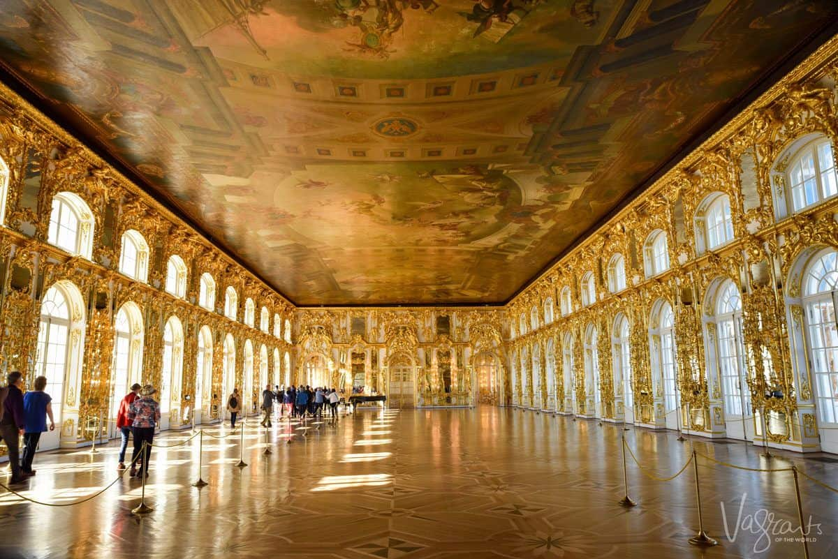 Golden room with light spilling through the archways and people looking at the painted ceilings and golden walls.  you will see these things in Russia if you go on a viking river cruise and cruise St Petersburg to Moscow