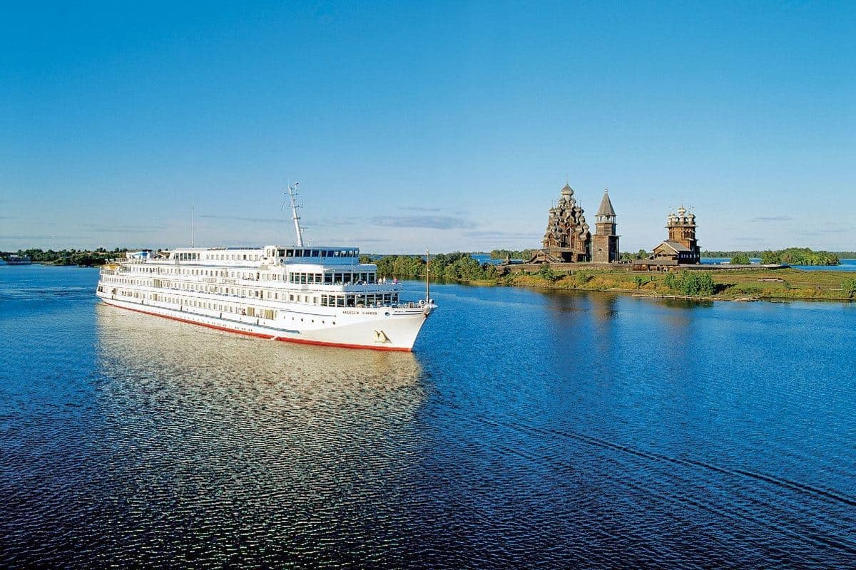 Viking river boat with temple on an island in the background.  River cruises in Russia are popular and a viking river cruise from St Petersburg to Moscow is the best way to see Russia