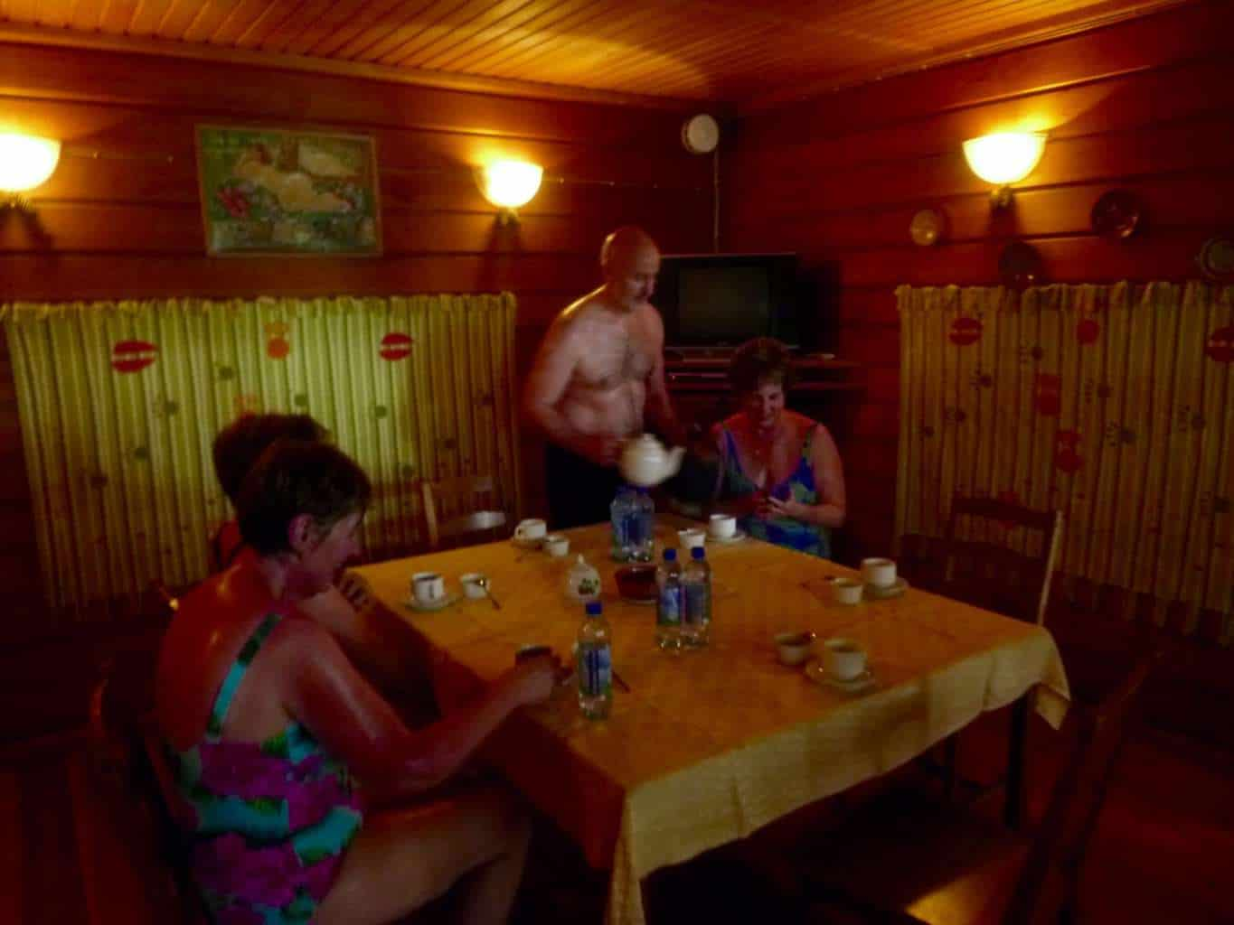 Traditional Russian Banya Mandrogy with man serving tea to two viking guests after being in the banya.  this really is a unique thing to do in russia