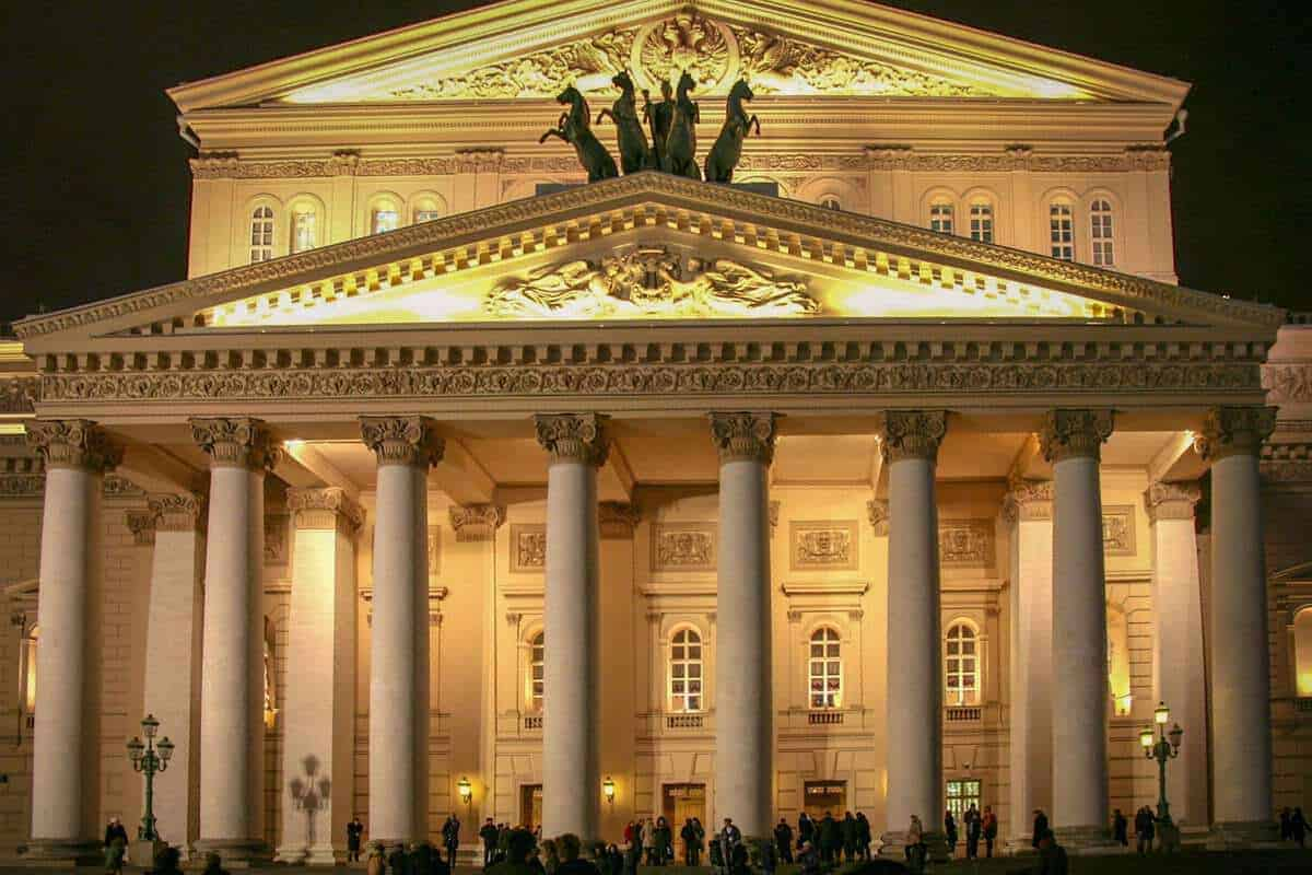 The Bolshoi Theatre Moscow Russia with the white flower garden in the foreground.What should a traveler visiting Moscow know about visiting the ballet. That it is a mandatory item on your travel schedule.