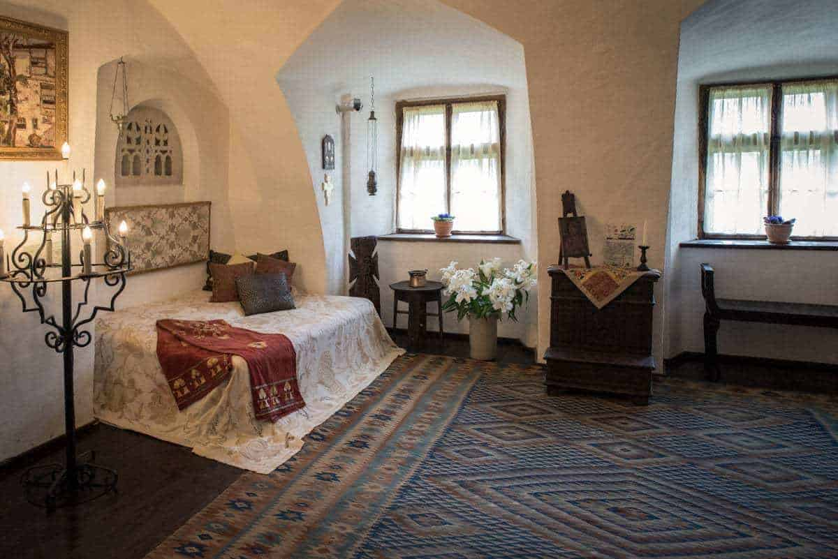 A large bedroom and candelabra inside Bran Castle Transylvania Romania. unique things to see and do in Romania