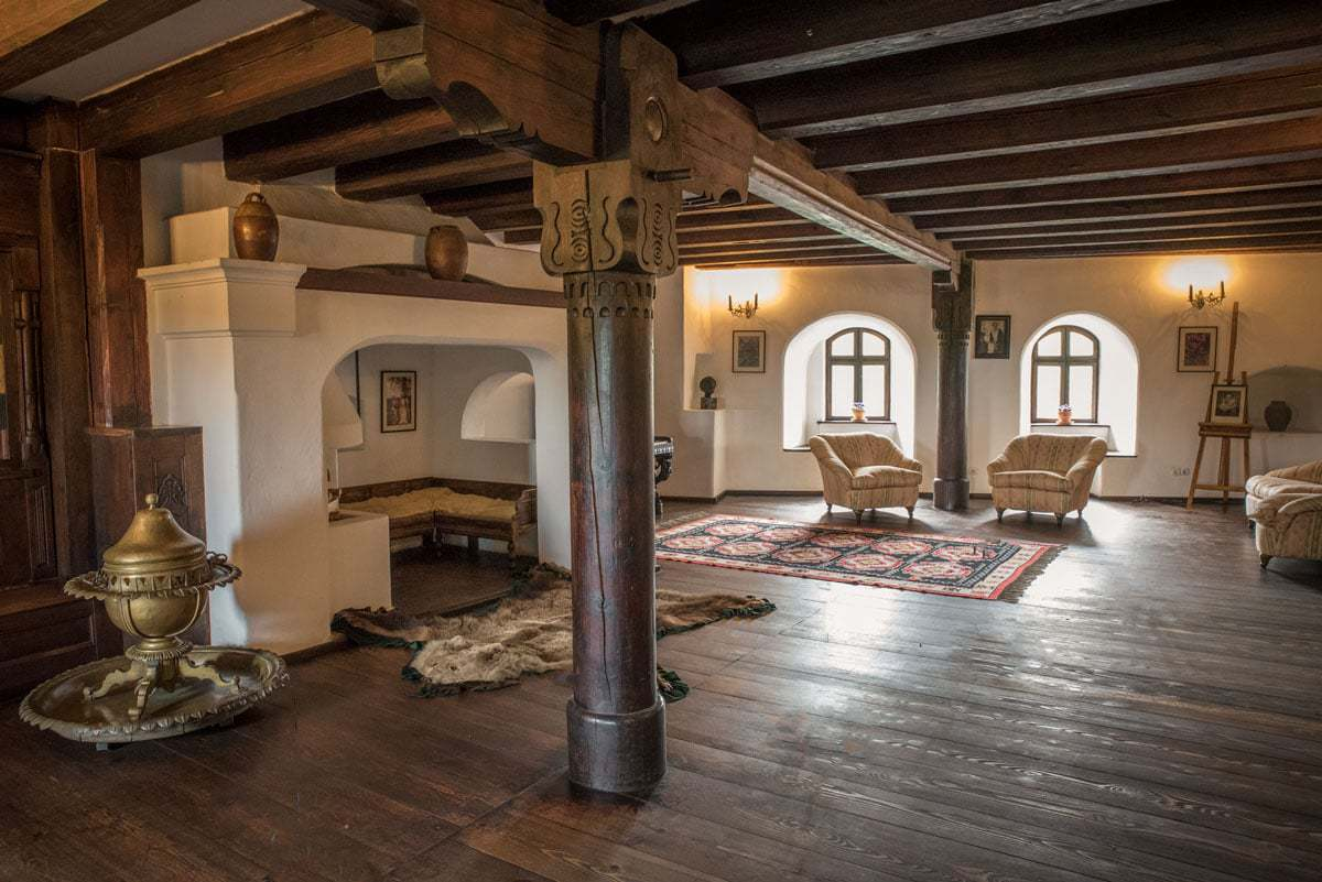 A lounge and fireplace inside the wooden rooms of dracula's castle romania, best things to see and do in romania