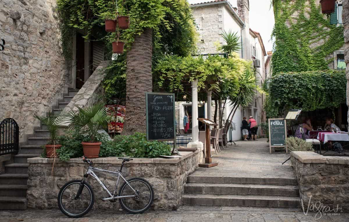 Typical restaurants draped with vines in old town Budva Montenegro.