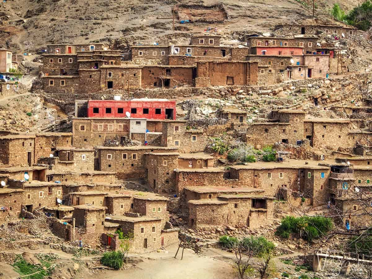Heading to the sahara desert on a moroccan road trip, Marrakech to Fez Atlas Mountains with traditional stone houses built into the hillside.