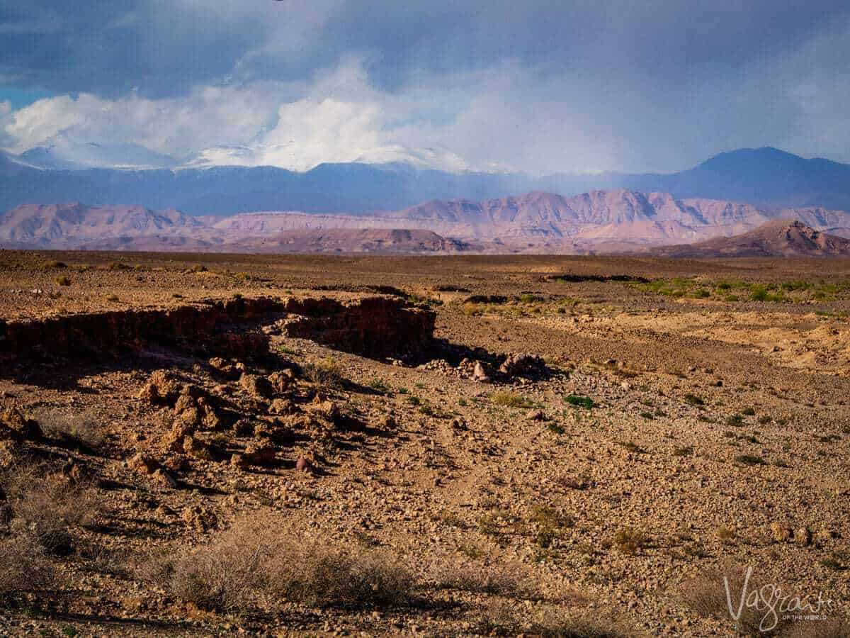 A desert scene with the mountains in the background under an angry stormy sky whilst on a moroccan road trip from Marrakech to Fez Atlas Mountains