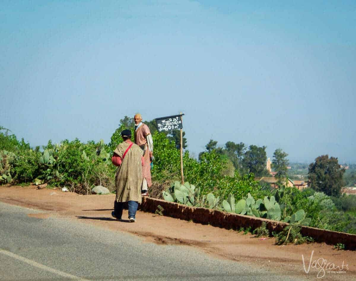 moroccan road trip, Marrakech to Fez Atlas Mountains with 2 local men on the side of the roads with cactus growing wild along the sides.