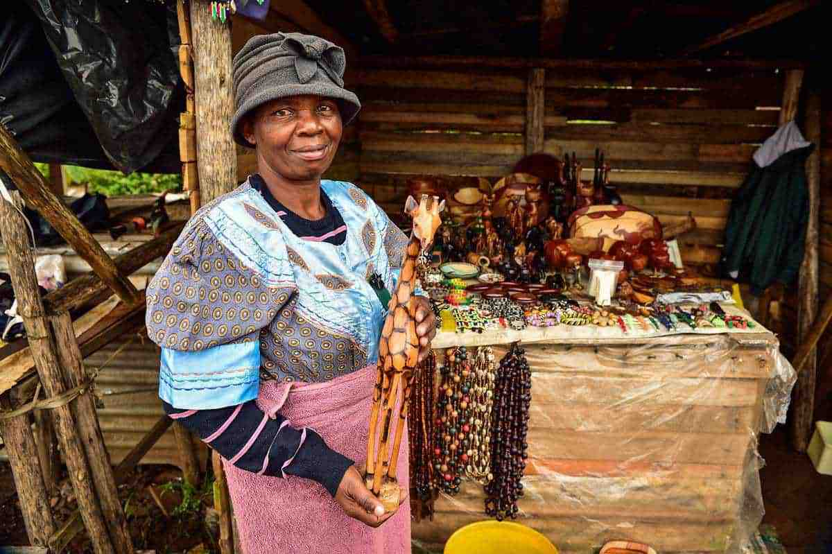 Souvenir seller holding a wooden giraffe in Graskop South Africa. It is always nice to support the local traders during your panorama route itinerary.