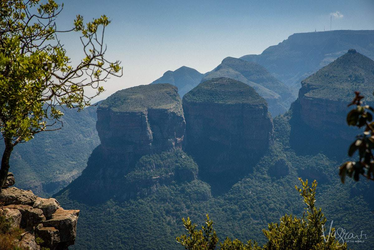Three Rondavels covered in green vegetation and shaped like round blocks rising up from the ground. The panorama Route is one of the best places to explore in South Africa.