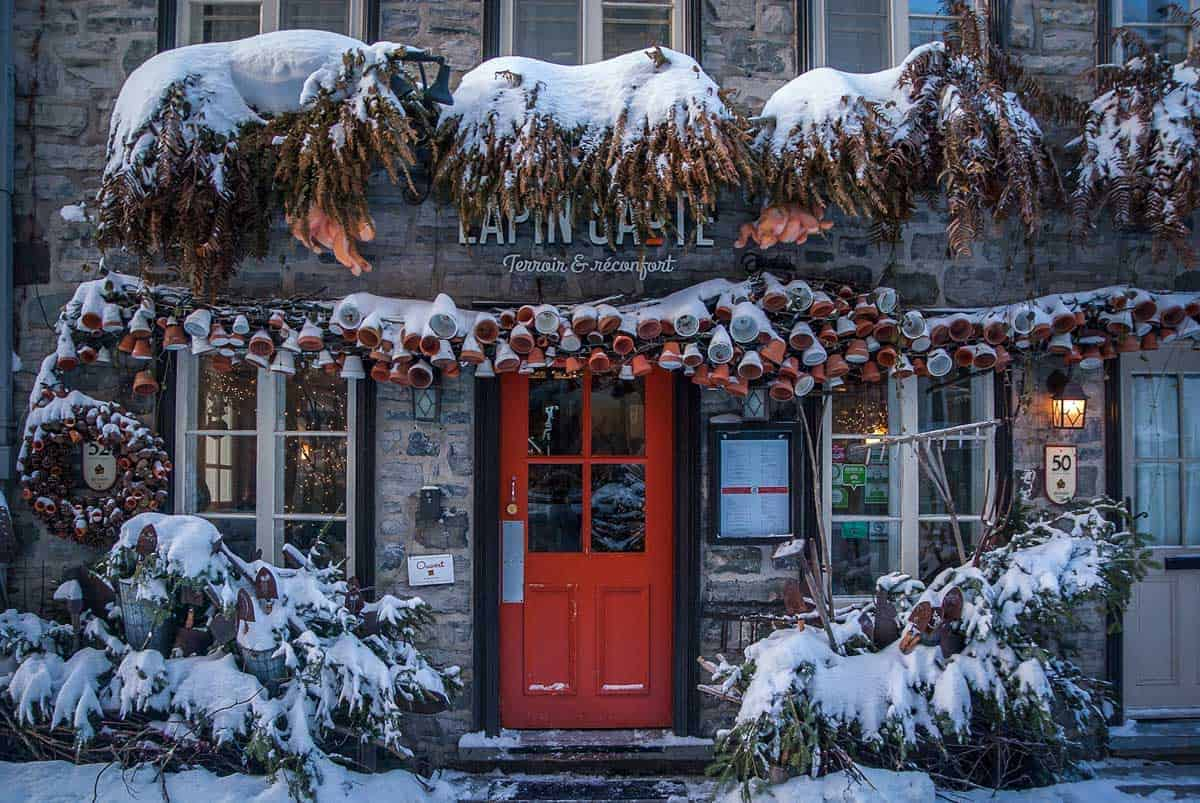 A red door of a hotel framed by snow in Quebec Old Town. This is what makes Quebec one of the best places to visit in eastern Canada