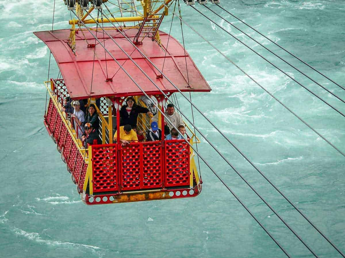 A group of slight scared people in a red Whirlpool Aero Car dangling over the swirling waters of Niagara Falls. A great reason to visit Canada.