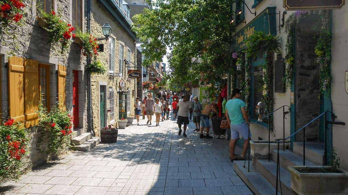 People strolling down a street in Old town Quebec. the street is lined with flowers growing from planters on old stone buildings. A great free thing to do in Quebec and this is why Quebec is best places to visit in eastern Canada