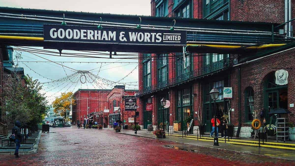 The red cobble stone streets in the Distillery District Toronto with the Gooderham and Worts Distillery sign overhead. It is this style that makes toronto the best places to visit in Canada