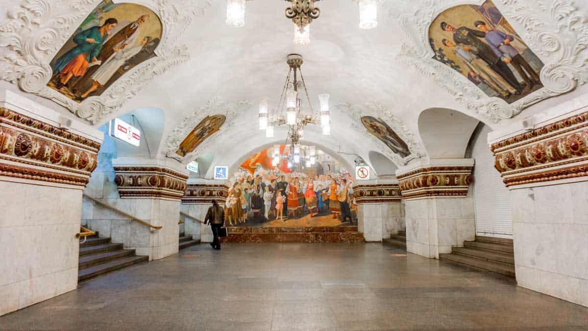 Man walking past the incredible mosaics in Kievskaya Station on the Moscow Metro.