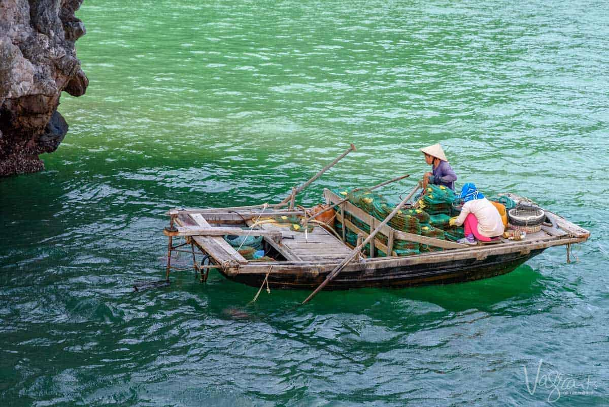 Women fishing in a small boat Halong Bay Vietnam