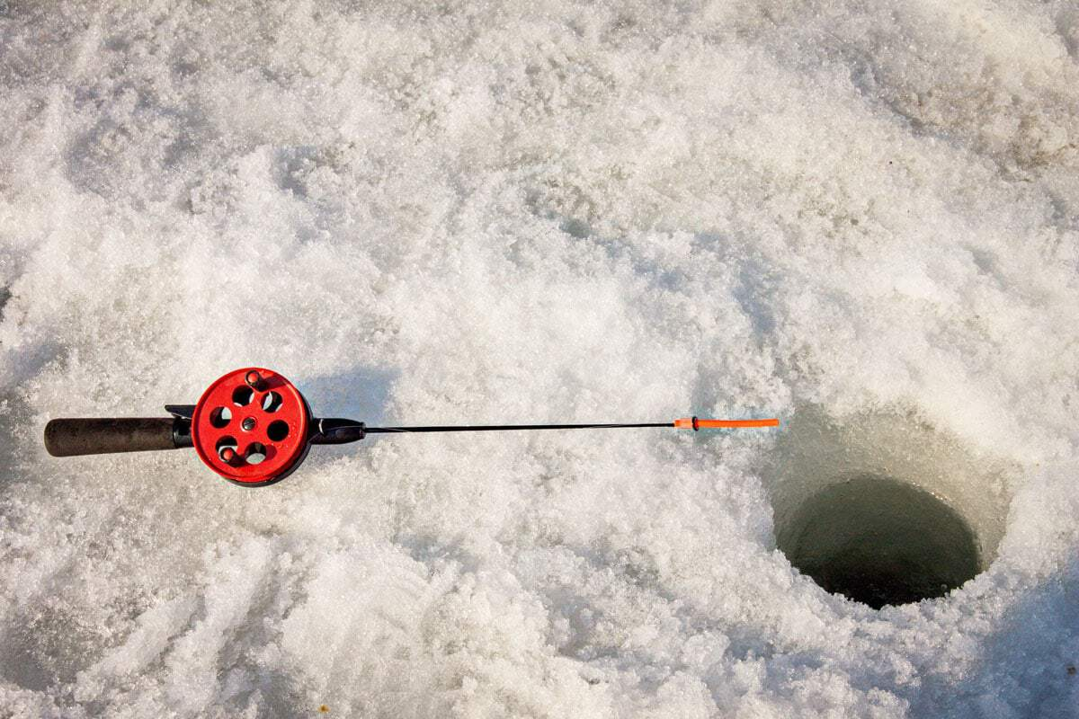 small fishing rod in snow next to a hole in the ice . Ice fishing in Finland - Things to do in winter in Europe
