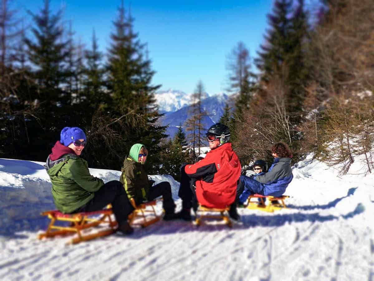 Family tobogganing in the snow in Tyrol Austria