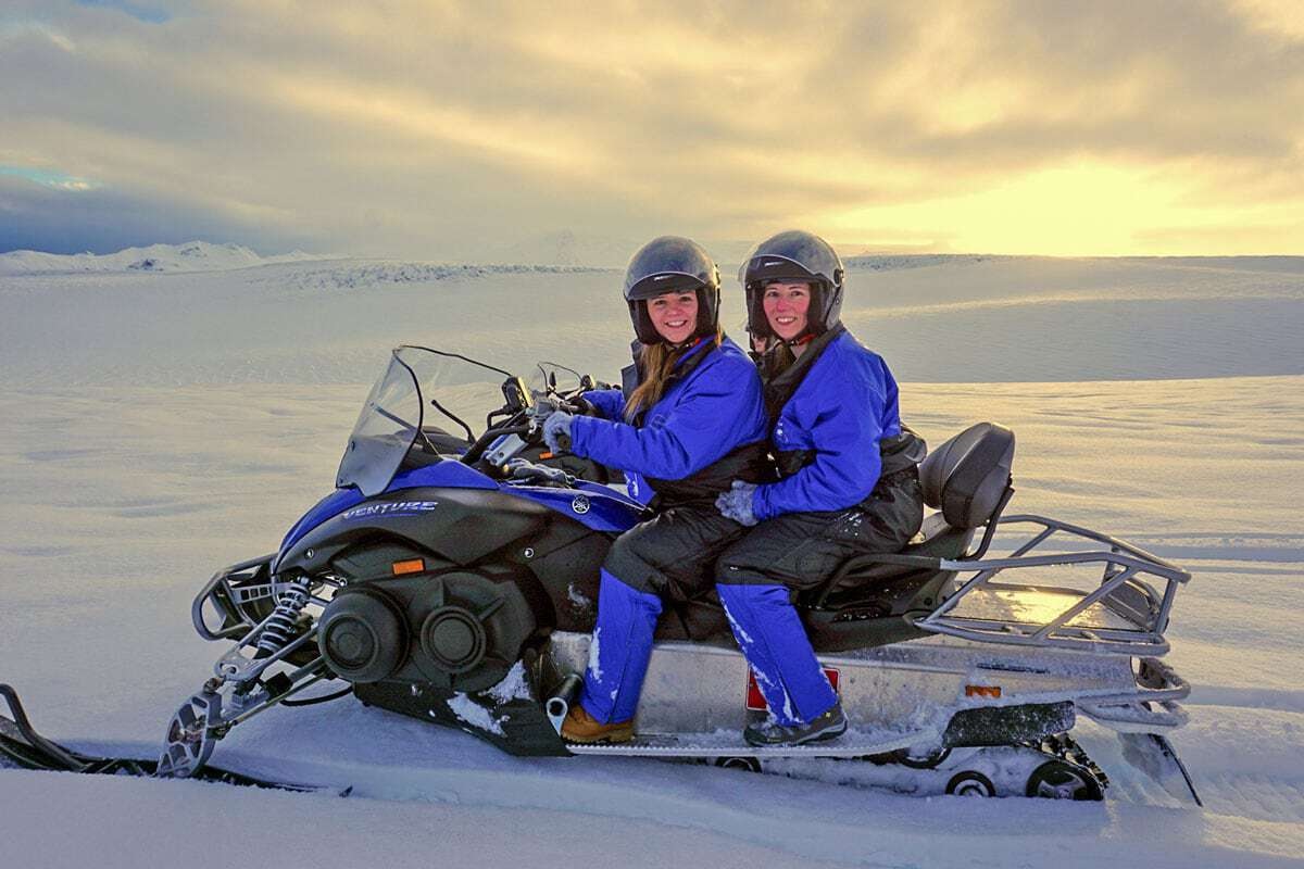 2 women sitting on a snowmobile in finland in winter - Activities to do in Finland in Winter